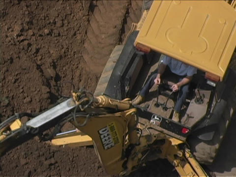 A John Deere Caterpillar moves dirt Stock Video Footage