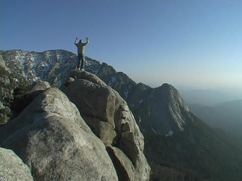 A hiker achieves his victory when he reaches the mountains summit Footage