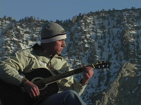 A man plays guitar on top of a mountain summit Stock Video Footage