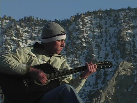 A man plays guitar on top of a mountain summit Footage