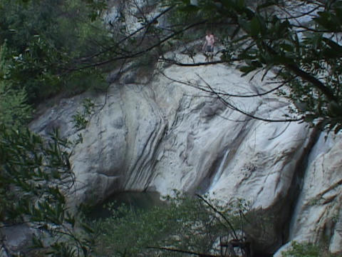 A man slides into a mountain pool Stock Video Footage