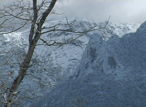 Dense clouds cover the peaks of snow covered mountains Stock Video Footage