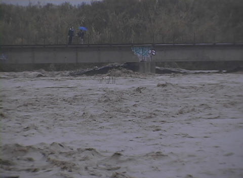 people stand on a bridge above a flooding river Footage