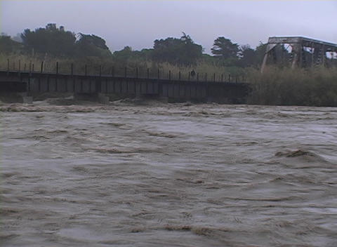 A man stands on a bridge above a flooded river Stock Video Footage