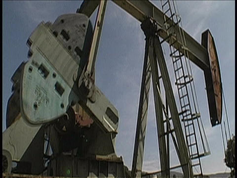A derrick pumps oil Stock Video Footage