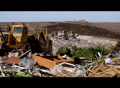 A large machinery moves through a garbage dump Live Action