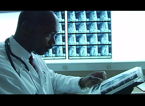 A doctor does research in a book with x rays in the background Footage