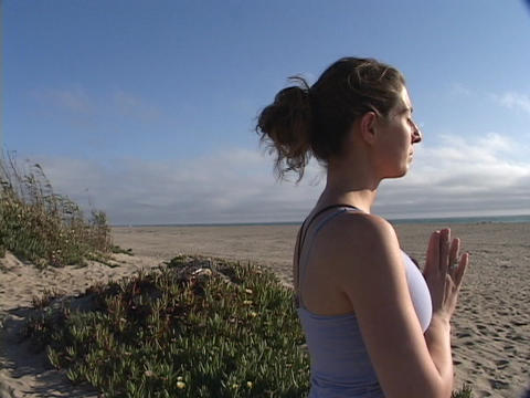 A woman practices yoga on a beach Stock Video Footage