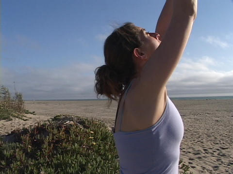 A woman practices yoga on a beach Footage