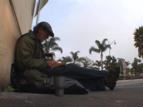 A homeless man lounges on the street corner Footage