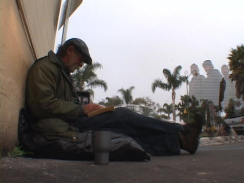 A homeless man lounges on the street corner Stock Video Footage