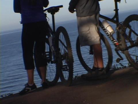 Mountain bikers overlook the ocean Footage