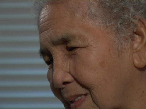 An old woman turns her head and smiles Stock Video Footage