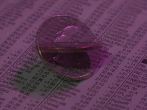 A quarter spins on the stock page of a newspaper Footage