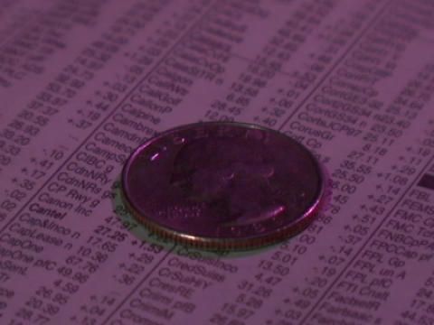 A quarter spins on the stock page of a newspaper Stock Video Footage