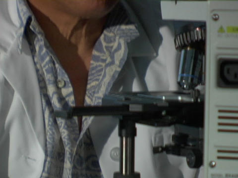 A man in a white coat adjusts a knob on a microscope Footage