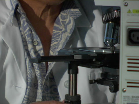 A man in a white coat adjusts a knob on a microscope Stock Video Footage