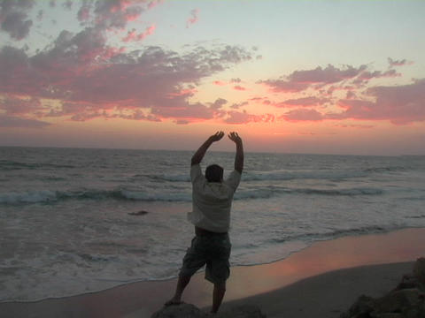 A man standing on the beach stretches his arms into the air Footage