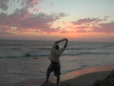 A man standing on the beach stretches his arms into the air Stock Video Footage