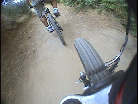 A mountain bike follows another biker on a dirt trail Stock Video Footage