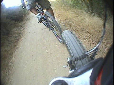 A mountain bike follows another biker on a dirt trail Footage