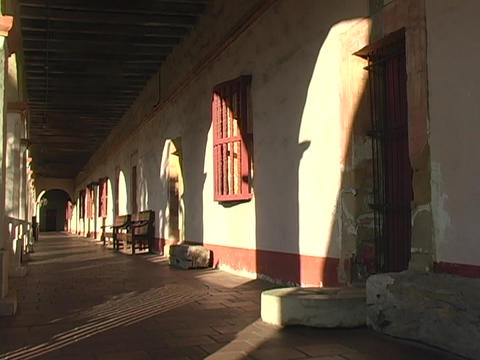 Light shines onto the portico and doorways of a Catholic mission in Santa Barbara, California Footage