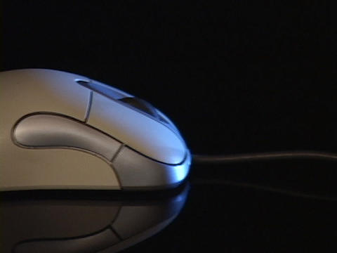 A cord extends from the back of a computer mouse Footage