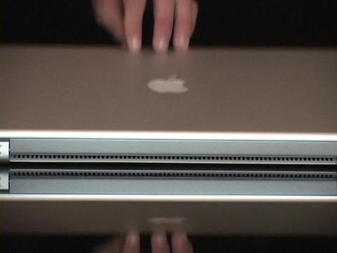 A hand closes an Apple Powerbook Footage