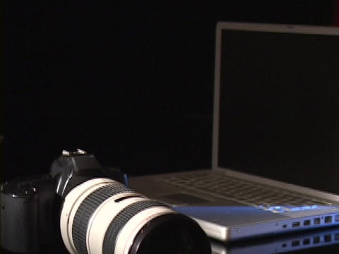 A digital camera rests on a table next to a laptop Footage