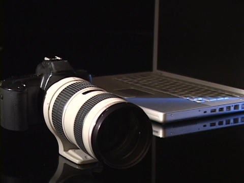 A digital camera rests on a table next to a laptop Stock Video Footage