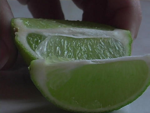 A chef slices a fresh lime into wedges Footage