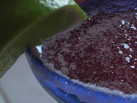 A bartender places a lime wedge on the salt rimmed edge of a margarita glass Footage