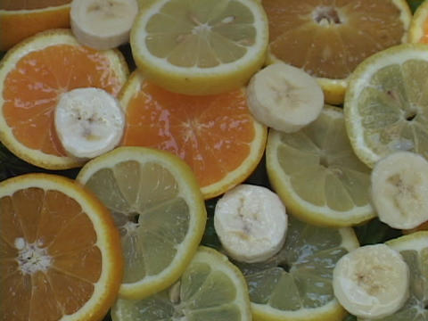 Water drips on slices of lemons, oranges, and bananas Stock Video Footage