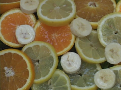 Water drips on slices of lemons, oranges, and bananas Footage