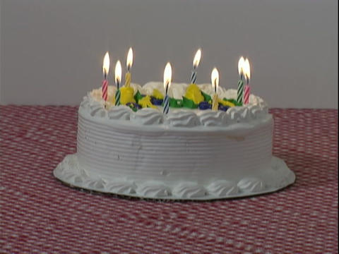 Candles burn down on a white birthday cake Live Action