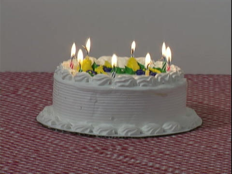 Candles burn down on a white birthday cake Stock Video Footage
