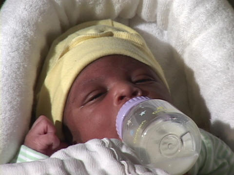 A newborn baby suckles milk from a bottle Stock Video Footage