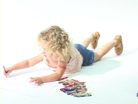 A little girl draws with crayons on a white paper Stock Video Footage