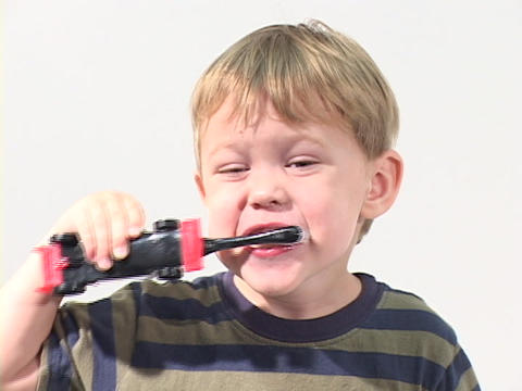 A boy brushes his teeth with an electric toothbrush Stock Video Footage