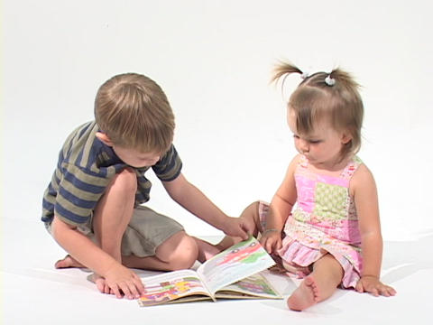 children read a book in a white room Stock Video Footage