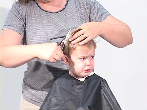 A boy gets his haircut at a barbershop Stock Video Footage