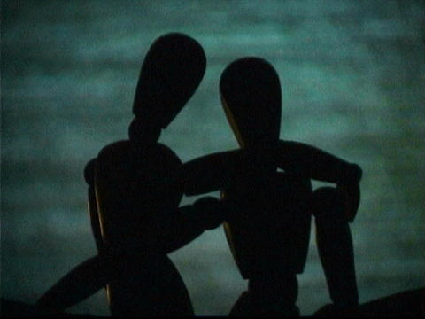 A television screen flashes behind entwined mannequins Stock Video Footage
