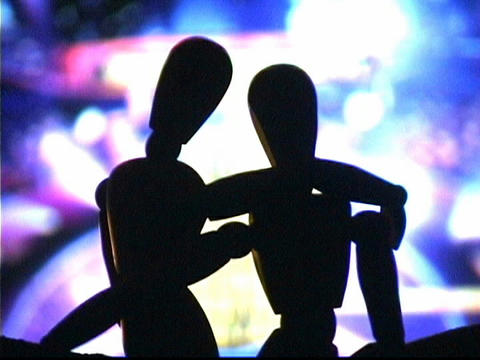 A television screen flashes behind entwined mannequins Footage