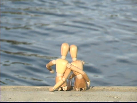 Entwined mannequins sit near the ocean Stock Video Footage