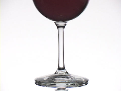 A glass of red wine rests on a white table Stock Video Footage