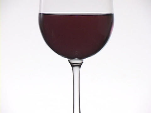 A glass of red wine rests on a white table Footage