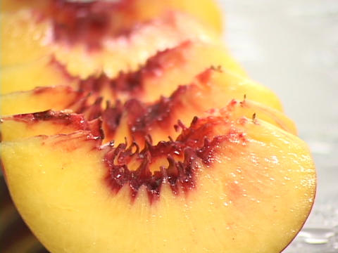 Freshly sliced peaches rest on a table Footage