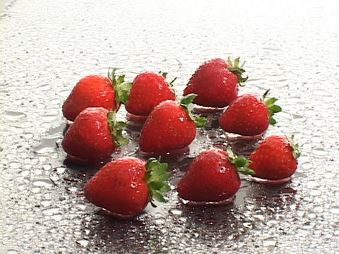 Fresh strawberries occupy a dewy surface Stock Video Footage