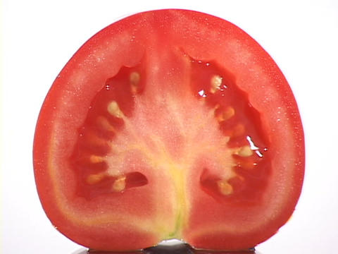 A tomato slice rests on a white surface Live Action
