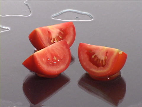 Fresh tomato wedges slide across a wet surface Footage